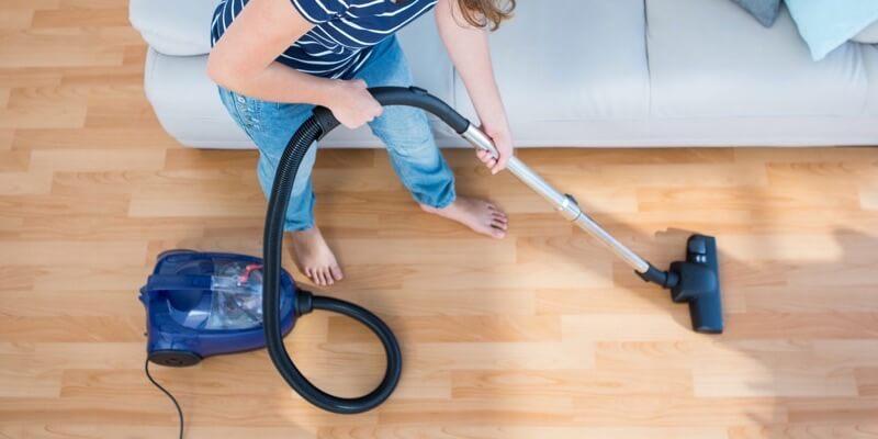 femme utilise aspirateur puissant sur sol dur